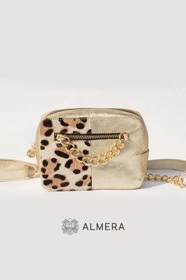 Elaborada en cuero dorado con apliques en cuero leopardo. Correa de cuero dorado con cadena bañada en oro Cierre de metal dorado Broche de metal dorado en la parte posterior de la correa  Medidas: Largo :15 cm Alto: 11 cm Profundidad: 5cm