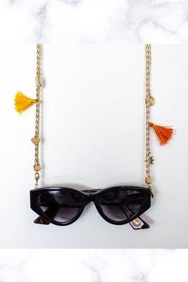 Colgador de lentes cadena dorada y detalles de color naranja y . amarillo.  75 cms.  CONSEJOS DE CUIDADO: Guardar por separado en un lugar seco y libre de polvo. Limpiar con un paño suave y seco. No usar limpiadores de ningún tipo. Evitar el contacto con el agua, perfumes, cremas, químicos, piscina o mar.