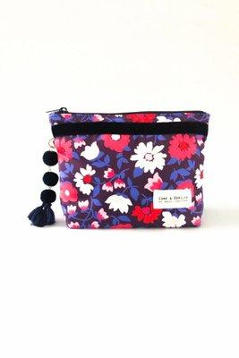 Es un neceser pequeño ideal para llevar en la cartera.  Las medidas son 21cm de ancho x 15cm de alto x 5cm de fuelle.  Interior de tela.  El color es morado con flores rosdas y blancas.