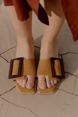 Sandalias de cuero con una hebilla de acrílico.  El color es amarillo mostaza.