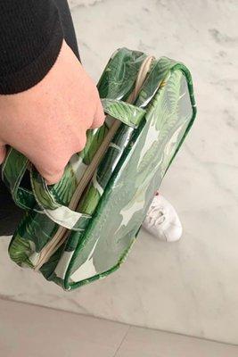 Medida: 29 cm de ancho x 23 cm de alto y 9cm de fuelle. Tela estampada en palmeras plastificada por fuera e impermeable por dentro. Cuenta con dos separaciones interiores, una de plastico transparente para evitar derrames y la otra de malla para poder ver lo que tenemos dentro.