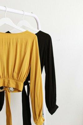 Blusa corta de cuello ojal y manga larga.  Detalles: • Pretina gruesa en la cintura. • Espalda descubierta. • Ojales y pretina larga en espalda. • 100% algodón
