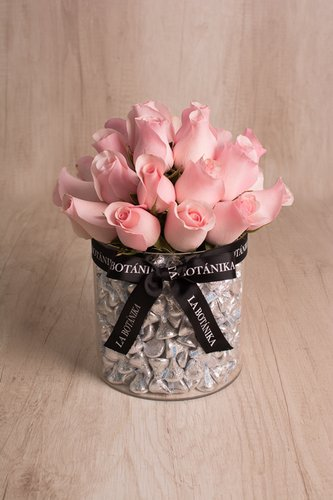 Base circular transparente rellena de 1 kilo de Kisses importados (chocolate de leche) + 21/25 rosas.  Medidas: 17cm x 17cm