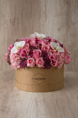 Caja redonda de material ecológico reciclado+ 12 Rosas rosadas + 3 Orquídeas+ Mix de Flores.  Medidas: 26cm x 12cm* Flores de temporada podrían ser reemplazadas por otras similares.