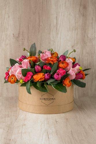Caja redonda de material ecológico reciclado + 10 Tulipanes+ 12 Rosas rosadas + Ranuculos naranjas + Mix de Flores.  Medidas: 26cm x 12cm* Flores de temporada podrían ser reemplazadas por otras similares.
