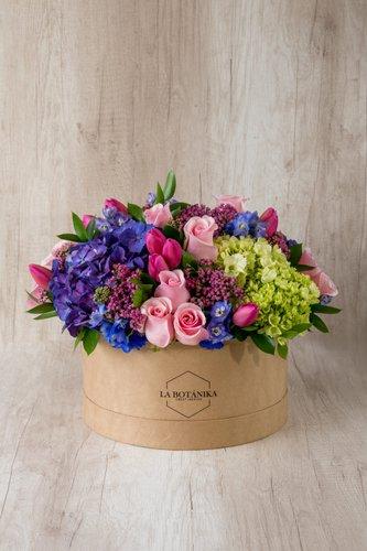 Caja redonda de material ecológico reciclado + 10 Tulipanes + 12 Rosas + Mix de Flores (Hortensias, ruscus, etc)  Medida caja: 26cm x 12cm  * Flores de temporada y color de tulipanespodrían ser reemplazadas por otras similares.