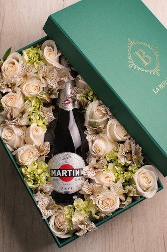 Caja verde + 12 rosas + Mix de flores + Botella.  Medidas: 36cm x 23cm  *Flores de temporada podrían ser reemplazadas por otras similares.