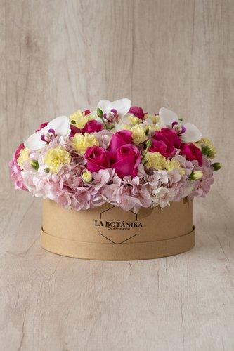 Caja redonda de material ecológico reciclado + 18/24Rosas + 3 Flores de Orquídea +Mix de Flores (Hortensias, Claveles, etc)  Medida caja: 26cm x 12cm  * Flores de temporada podrían ser reemplazadas por otras similares.