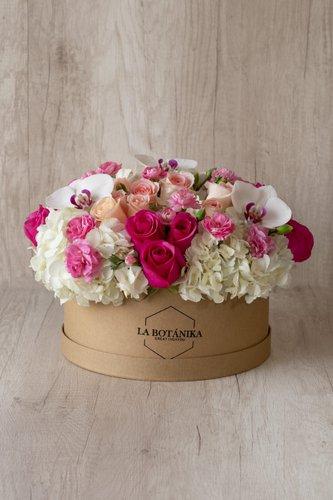 Caja redonda de material ecológico reciclado + 12Rosas + Mini Rosas +3 Flores de Orquídea +Mix de Flores (Hortensias, Claveles, etc)  Medida caja: 26cm x 12cm  * Flores de temporada podrían ser reemplazadas por otras similares.