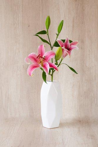 Florero de cerámica blanco+1 Lilium rosado.  Medidas florero: 28cm x12cm  *Para solicitar un color especifico, escríbenos a pedidos@la-botanika.com.