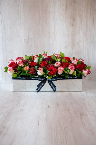 Base rectangular revestida de espejo + 36 rosas + Mix de flores  Medidas: 51cm x 18 cm  *Flores de temporada podrían ser reemplazadas por otras similares.