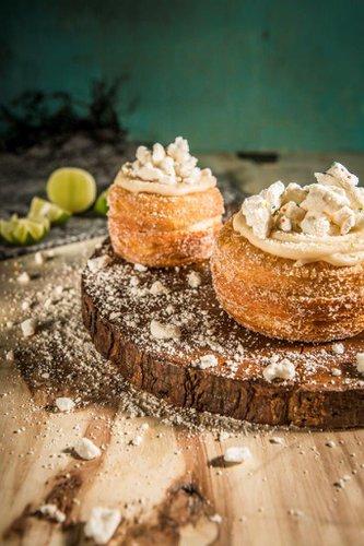Kroughnut rellena de ganache de limón, cubierta con glaseado de vainilla artesanal, merengues y ralladura de limón.