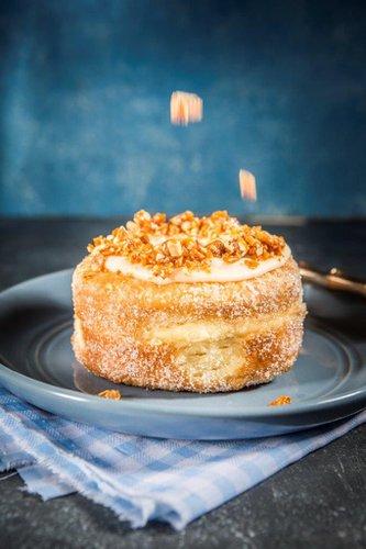 Kroughnut rellena de crema pastelera de vainilla, cubierta con glaseado de vainilla artesanal y praliné de almendras.