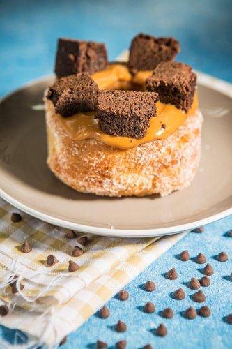 Kroughnut cubierta con manjar blanco de olla y brownie de chocolate hecho en casa.