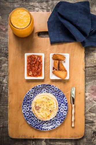 Bowl de pan Brioche hecho en casa, relleno con huevos revueltos, tocino ahumado, queso cheddar y queso mozzarella derretidos, cubierto con queso parmesano gratinado. Lo servimos con pan frito y fondue de tomate casero.