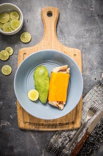 Burrito de tortilla de trigo relleno de huevos revueltos con pimientos verdes, cebolla blanca, tomate, champignones y queso mozarella. Envuelto en queso cheddar derretido acompañado con palta y limón.