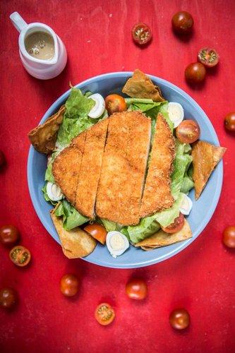 Pechuga de pollo crispy servida sobre lechuga orgánica con tomatitos cherry, huevos de codorniz, crumble de vainilla y tortilla chips. Aderezo: Honey Mustard.