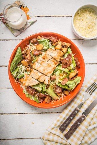 Pechuga de pollo a la plancha servida sobre lechuga orgánica con queso parmesano rallado, tocino ahumado, croutons y praliné de almendras. Aderezo: Vinagreta de la casa.