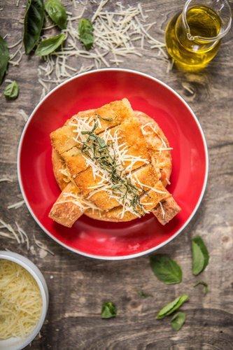 Kretzel servido con fondue de tomate casero sobre rodajas de tomate fresco, cubierto con queso mozzarella derretido y pechuga de pollo crispy acompañada de queso parmesano y albahaca.