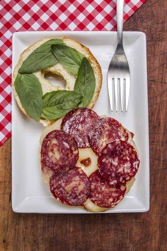 Salame húngaro servido sobre una base de fondue de tomate casero, queso mozzarella derretido y hojas de albahaca fresca. La recreación perfecta de una pizza en un bagel