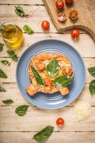 Kretzel servido con fondue de tomate casero sobre rodajas de tomate fresco, cubierto con queso mozzarella y queso parmesano derretidos, tomatitos cherry y albahaca.