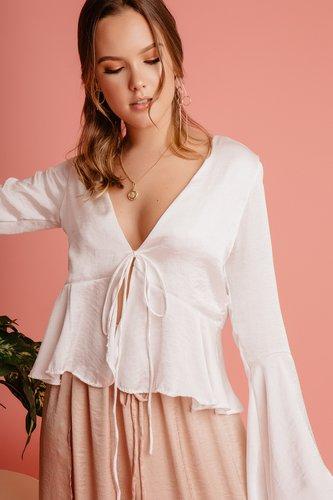 Blusa de seda con manga larga y lazo en la parte de adelante. Escote pronunciado.