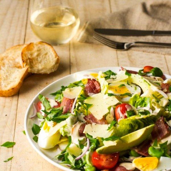 La ensalada César es una ensalada de lechuga romana, trocitos de pan tostado aliñados y queso parmesano. Además, lleva salsa blanca a base ajo.