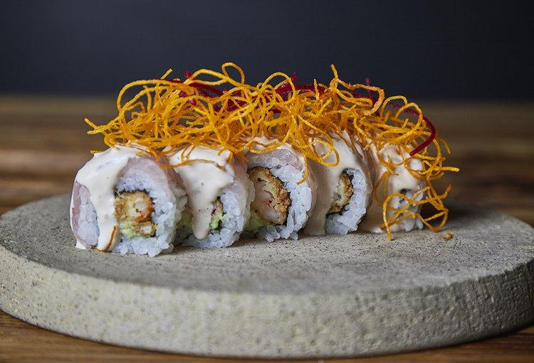 Clásico de nuestra barra, relleno de Ebi furai y palta, cubierto con láminas de pescado fresco, salsa acebichada e hilos de camote.