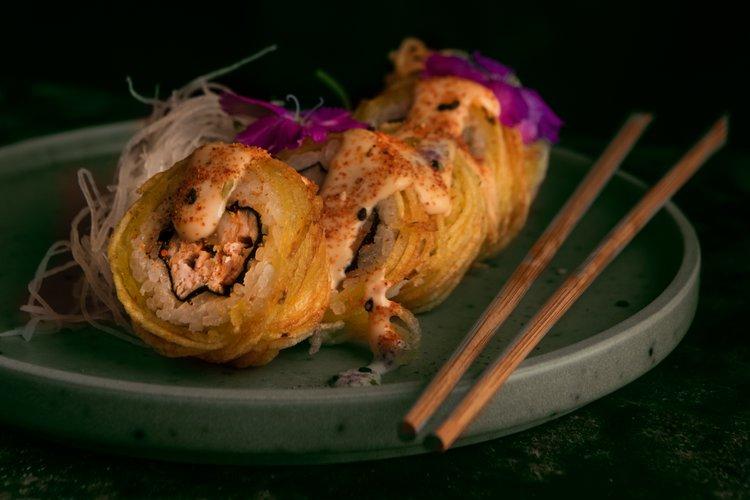 Maki relleno de ebi furai,palta y queso crema, cubierto con hilos de papa amarilla y salsa spicy mayo.
