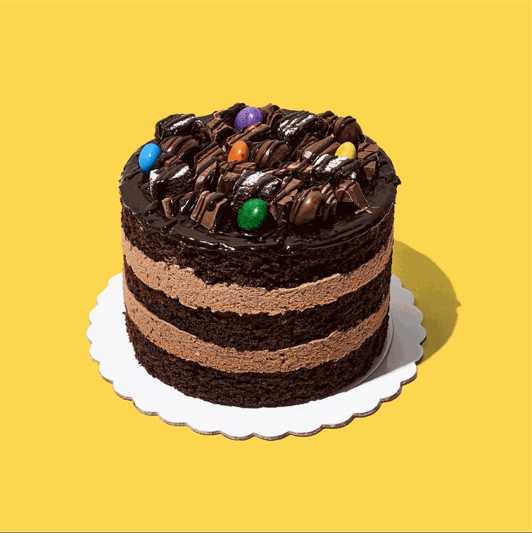 Mini torta con tres deliciosas capas de brownie y un exquisito doble relleno de queso crema sabor a chocolate, decorado con fugde, mini brownies y los más ricos chocolates.  Medida: 14 cm de diámetro, 9 cm de altura  Porciones: 6 a 8