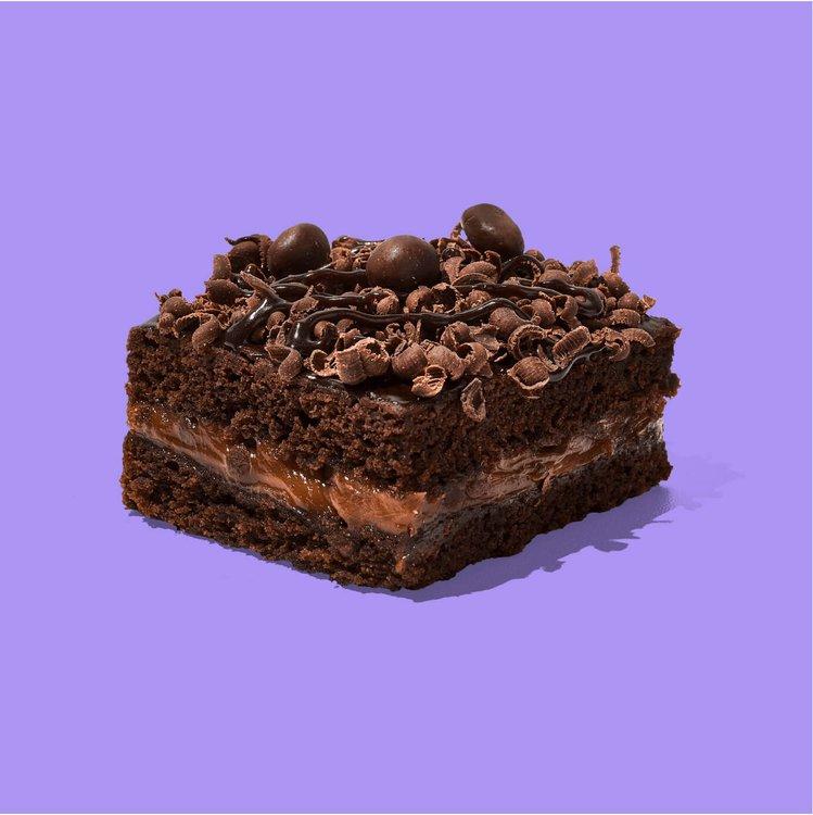 ¡Un Brownie para los amantes del chocolate! Brownie de chocolate con relleno de manjar y cobertura de chocolate en rulos, fudge y chocolate M&M.  Medida de Producto: 6.5 cm de ancho, 6.5 cm de largo, 3.5 cm de altura