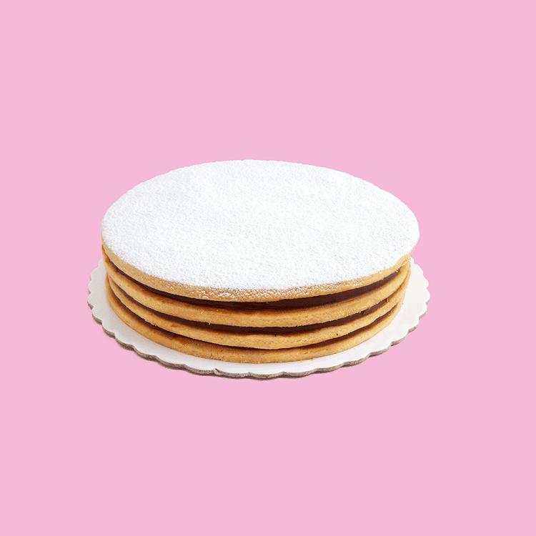 Alfajor con cuatro capas de galleta y triple relleno de manjar. Espolvoreada de azúcar impalpable. Medida: 20 cm de diámetro.