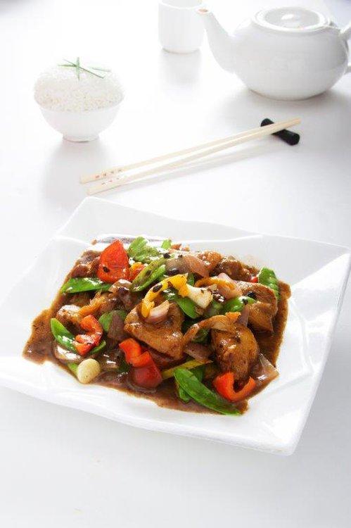 Pollo en trozos salteado con verduras en salsa tausi.