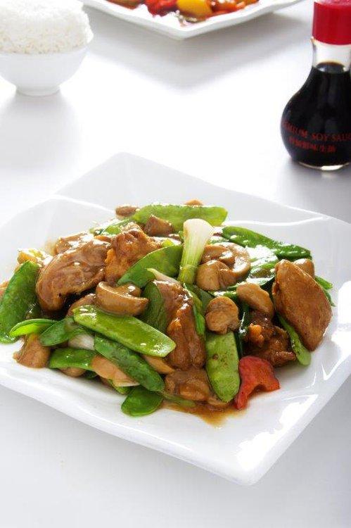 Un feliz encuentro en wok de trozos de pollo con holantao, pimiento y champiñones.