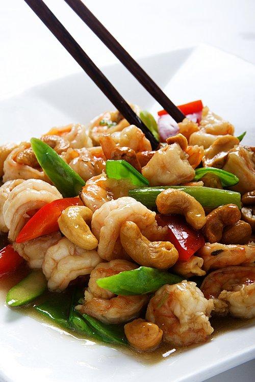 Langostinos salteados con verduras adornados de almendras chinas.