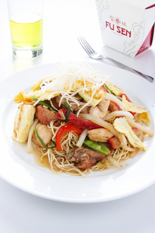 Trozos de pollo, cerdo y pato se hacen presentes en el wok. El tallarín es la base y una tortilla de huevo corona a este magistral plato.