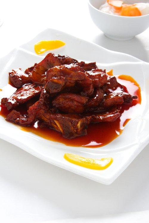 El toque dulce del KIN TU y la salsa de tamarindo cubren esta exquisita costilla frita de chancho.