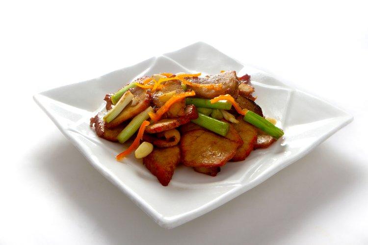 Nuestro chancho asado y salteado en wok con cebolla china y trozos de ajo.